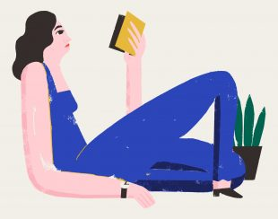 A woman in blue dungarees reading a yellow zine.