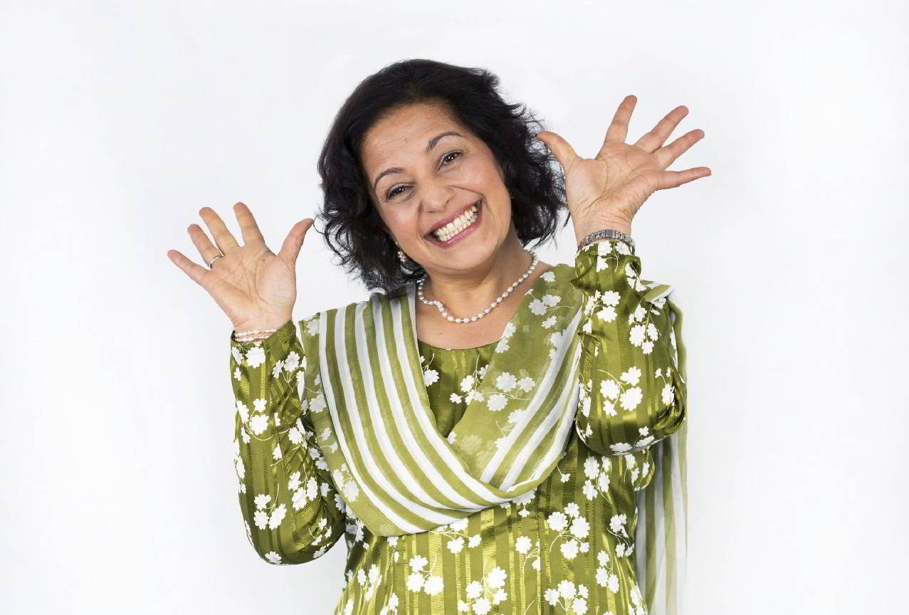 Woman with a big smile holding her hands up, palm to the camera, on either side of her face