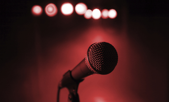 A microphone pictured up close. A red smokey background of a venue is pictured. And eight lights are seen on the very top of image, however out of focus.