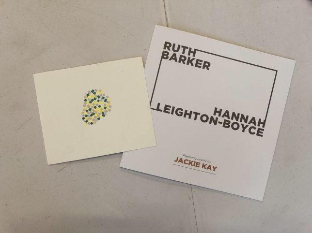 An exhibition catalogue with the names Ruth Barker and Hannah Leighton-Boyce sits on a white table. On top of the catalogue is a postcard. The postcard is an off-white and in the centre are lots of small paper sqaures grouped together. The squares are yellow and green and together look like the shape of a pear.