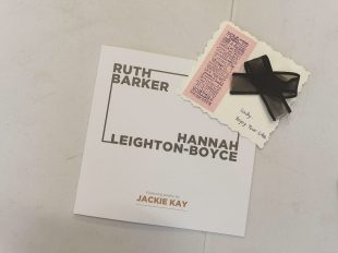 An exhibition catalogue with the names Ruth Barker and Hannah Leighton-Boyce sits on a white table. On top of the catalogue is a postcard. On the right hand side of the postcard is a big bow made of black ribbon, below it are the handwritten words 'Lady, enjoy your life.' On the left side of the postcard is a pink piece of paper on which a stamp has been used, the stamp is a long list of words including 'joy' 'dream' 'perfect' and 'love'.