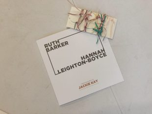 An exhibition catalogue with the names Ruth Barker and Hannah Leighton-Boyce sits on a white table. On top of the catalogue is a postcard. The postcard is an off-white colour and rectangular in shape. Tied around the postcard are lots of thin overlapping ribbons in different colours.