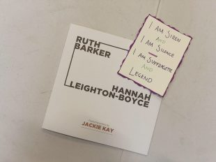 An exhibition catalogue with the names Ruth Barker and Hannah Leighton-Boyce sits on a white table. On top of the catalogue is a postcard. The postcard is off-white with a purple edge. In the centre are the handwritten words 'I am siren and I am silence. I am suffragette and legend'. The words are purple and green.