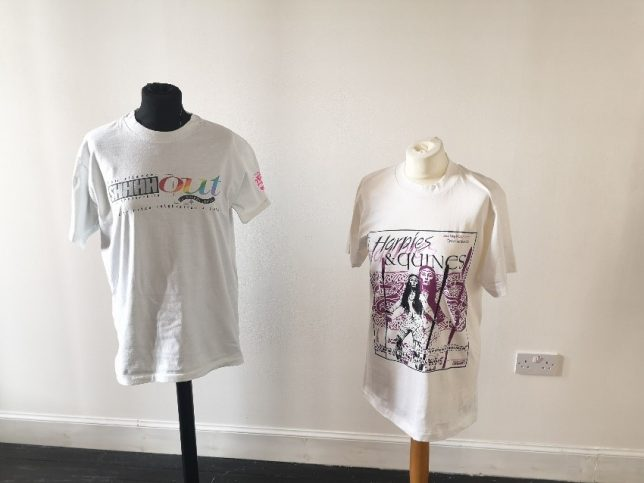 "Two t-shirts displayed side by side. The t-shirt on the left says ""Shhhh Out"" and the right-hand t-shirt shows the cover of an edition of Harpies and Quines."