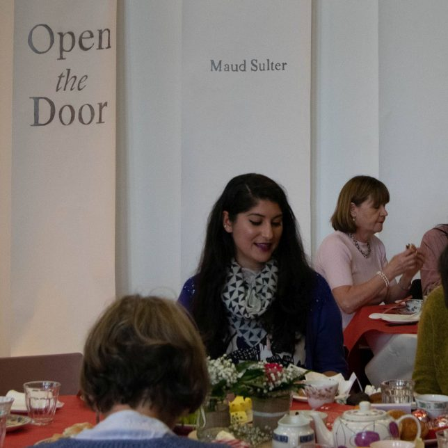 Women sitting around a table with teapots and cakes on it. Behind them is a banner that has 'open the door' cut out of it.