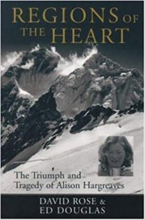 "The cover of Region of the Hearts is in black and white with a mountain in the background with cloudes above. A picture of Alison Hargreaves accompanied by the subtitle of the book "" The Triumph and Tragedy of Alison Hargreaves"" in black letters."
