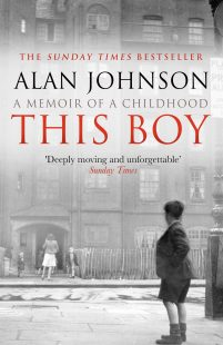 """A black and white backrground picture of a street with a woman walking into a house and a young boy looking at her in the foreground. The title of the book """"This Boy"""" is witten in big, red bold letters across the picture."""