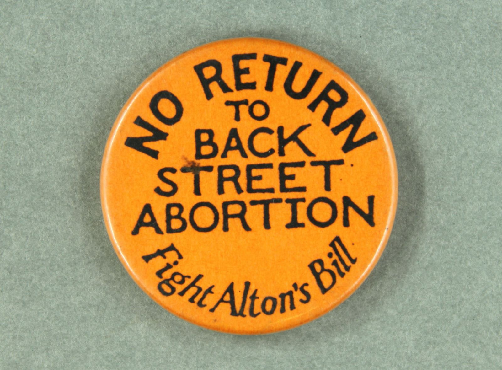 """An orange badge that has black text that reads, """"No Return to Back Street Abortions, Fight Alton's Bill""""."""