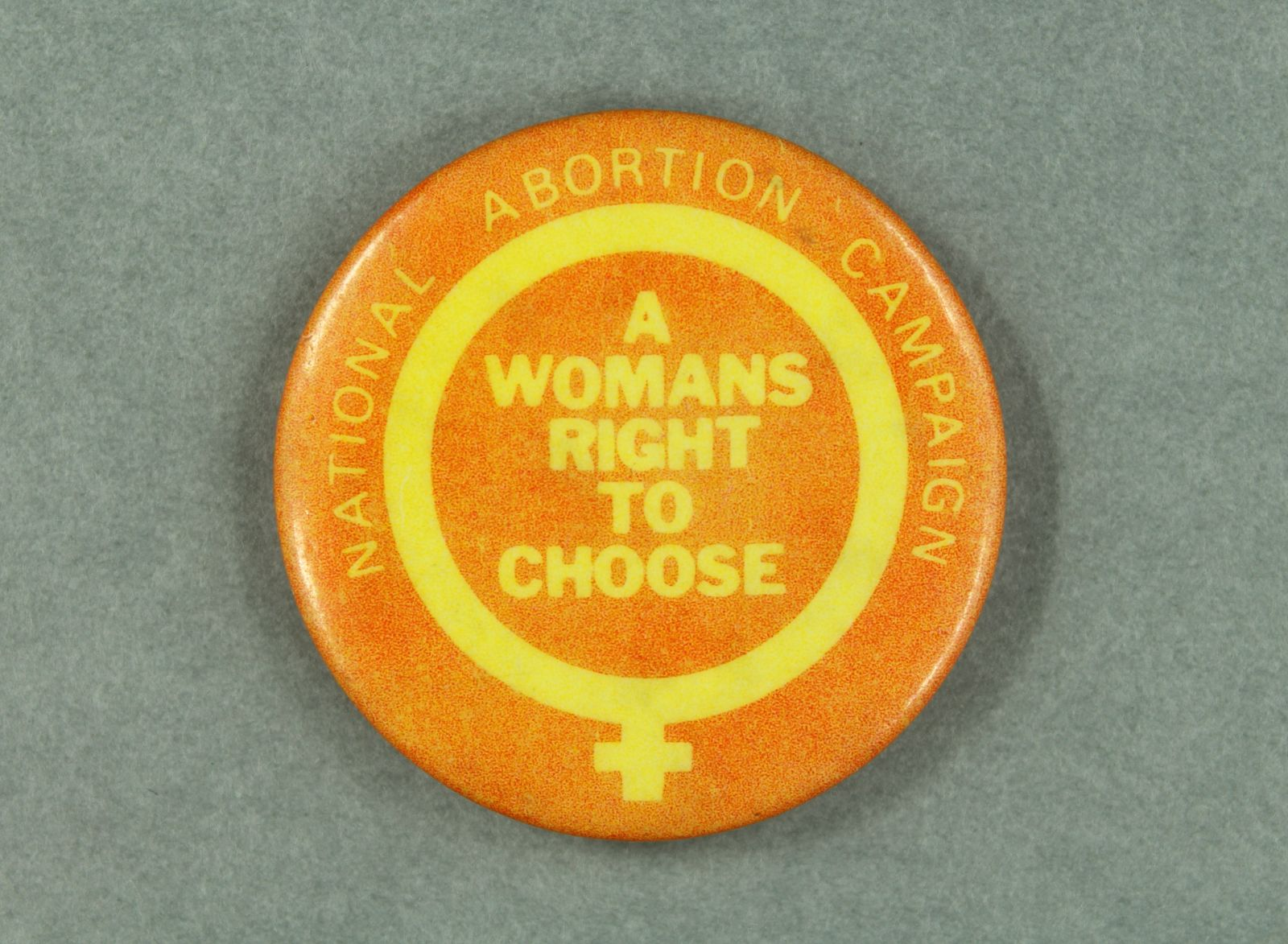 """An orange badge with a yellow symbol for 'woman' on it. In the centre of the symbol is the yellow text, """"A Womans Right to Choose""""."""