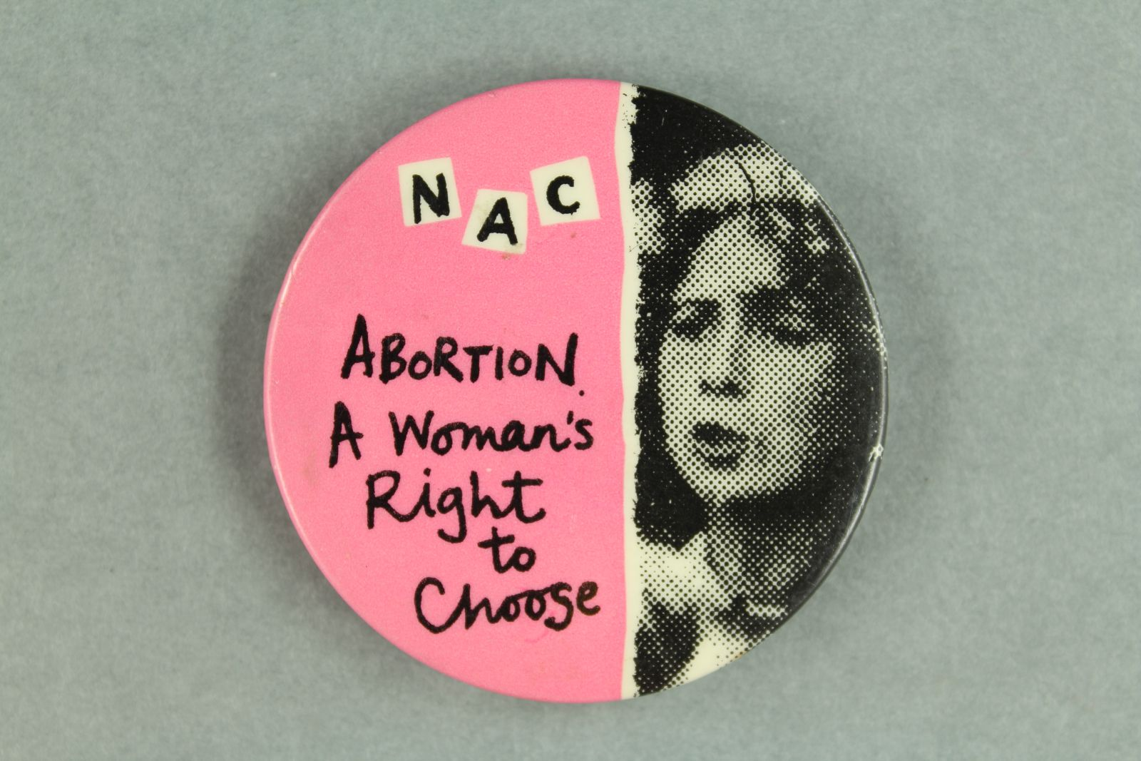 """A pink badge with a black and white image of a woman's face to the right. On the left is written, """"Abortion, A woman's right to choose""""."""