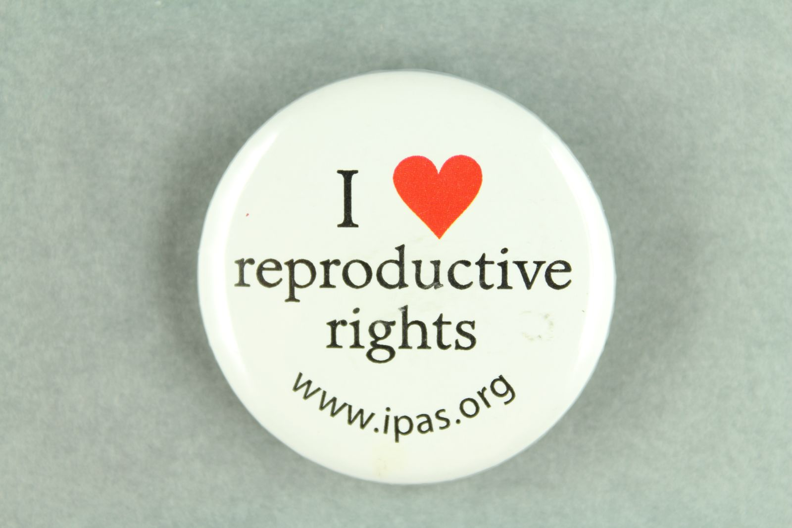 """A white badge with the text, """"I heart reproductive rights, www.ipas.org."""""""