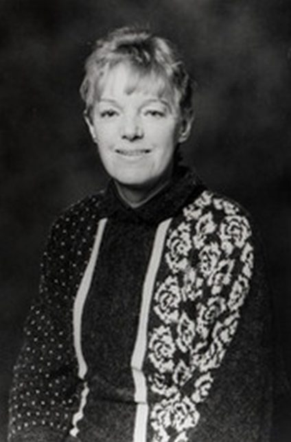 A black and white image of Agnes Owens. She is smiling at the camera and it appears the image was taken in a studio.