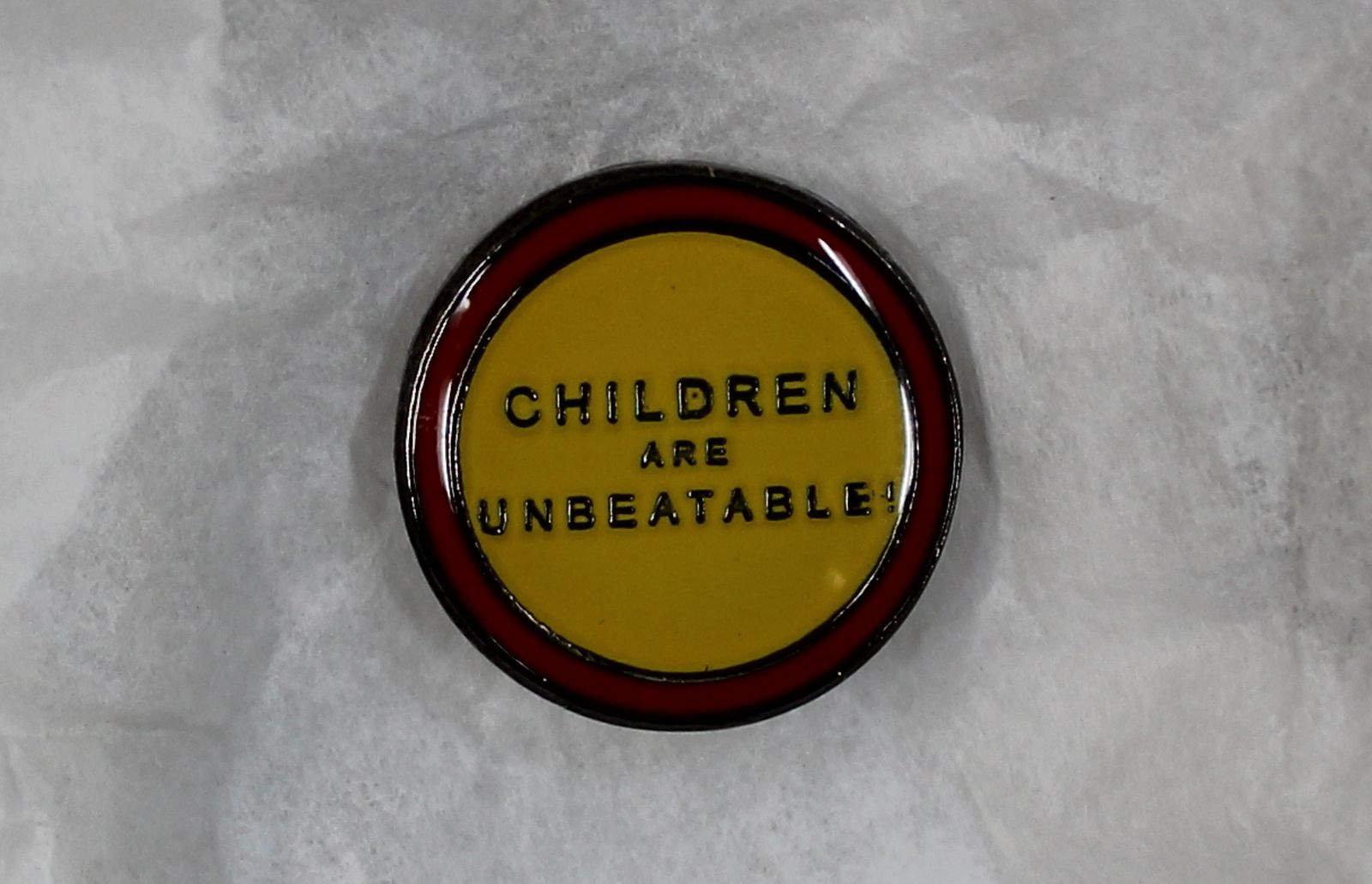 """An enamel badge with a yellow centre and a red band around its circumference. In the centre the words, """"Children are unbeatable"""" are written in block capitals."""