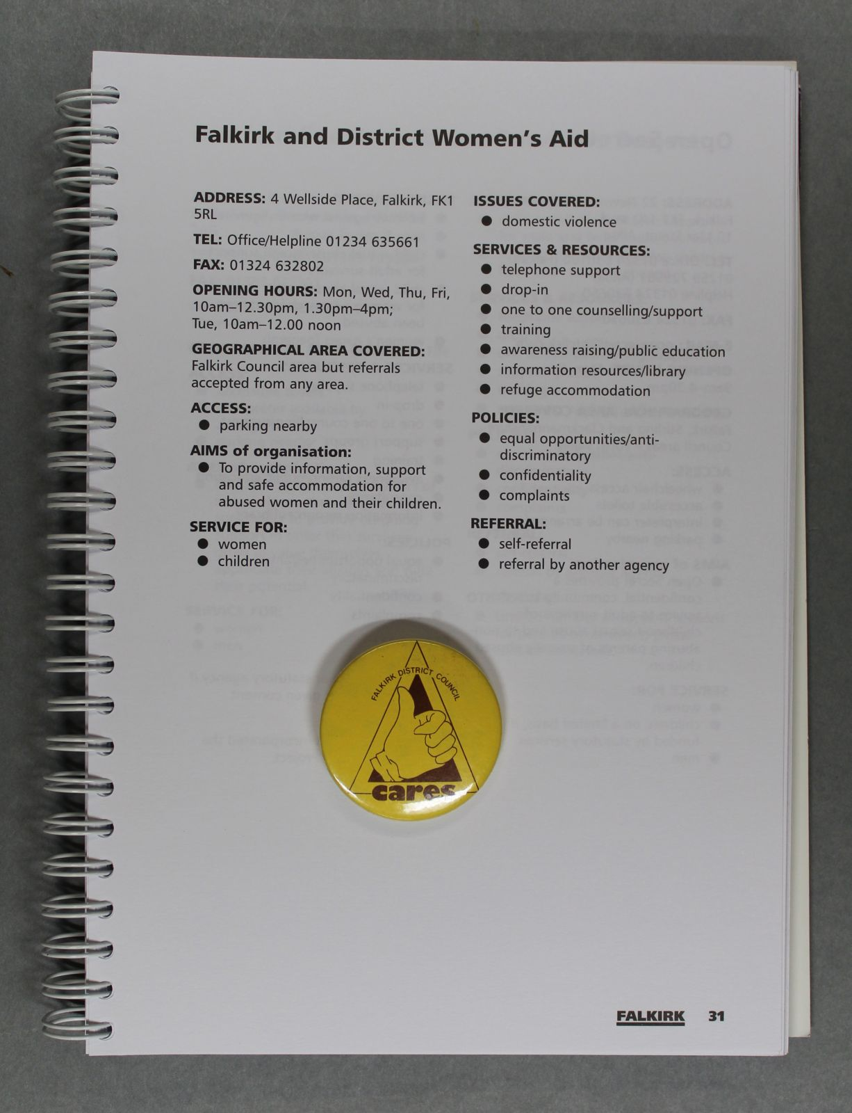 A yellow 'Falkirk District Council Cares' badge on top of an entry from a book that gives information on Falkirk and District Women's Aid