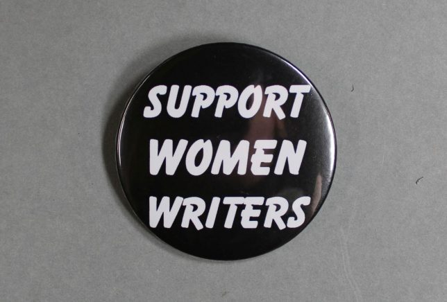 """A black badge with the text, """"Support Women Writers"""", printed in white."""