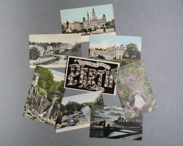 """Postcards from the collection showing different buildings and landscape, including a """"Greetings From Fife"""" postcard in the centre."""
