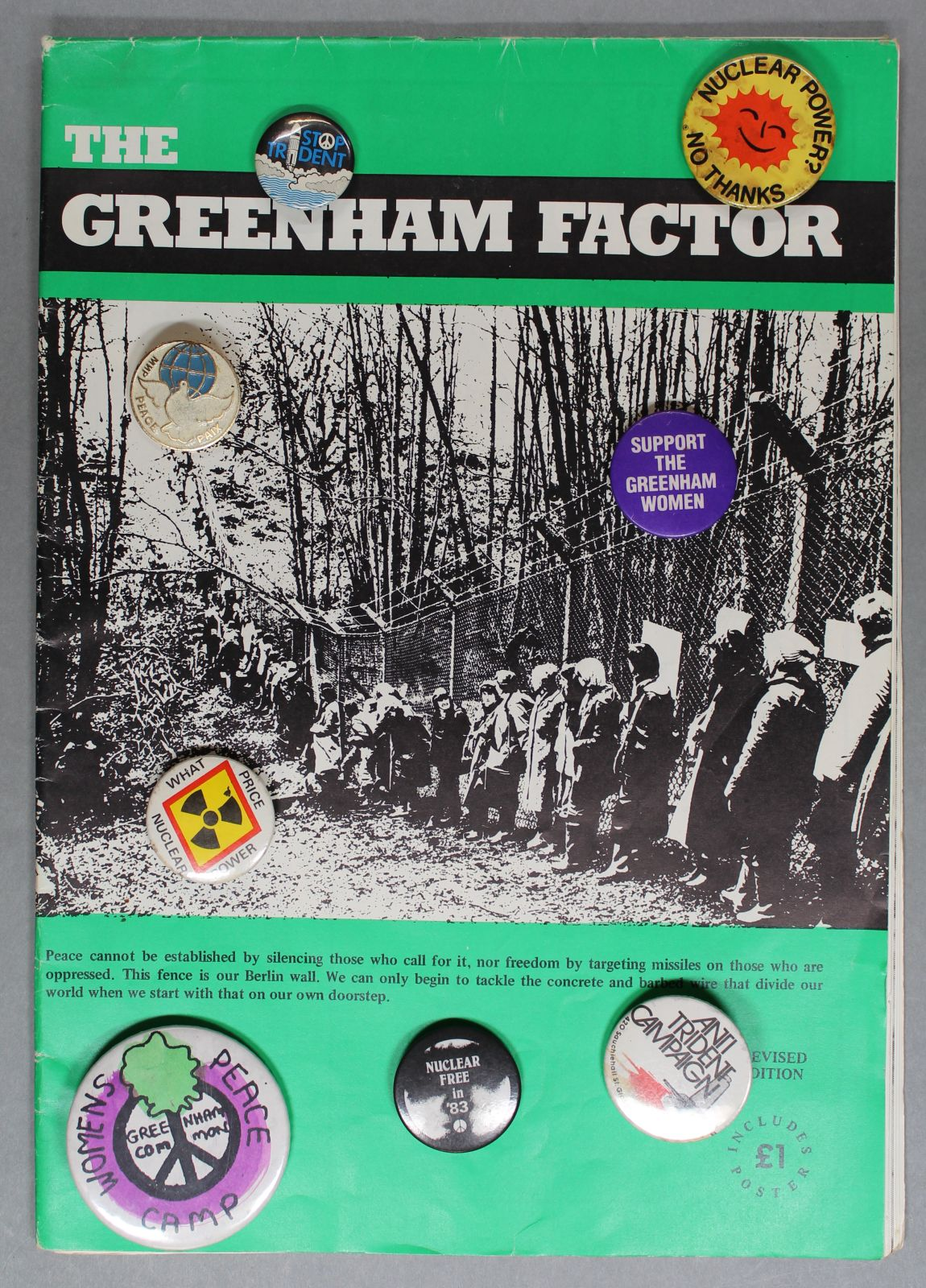The Greenham Factor booklet with anti-nuclear and peace campaign badges sitting on top of it.