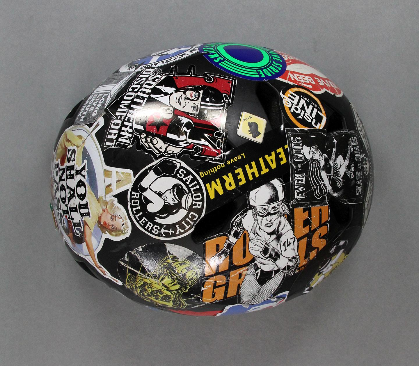 Skate helmet donated by skater Deadly DeVito #0.5. The helmet is covered in colourful roller derby and brand stickers