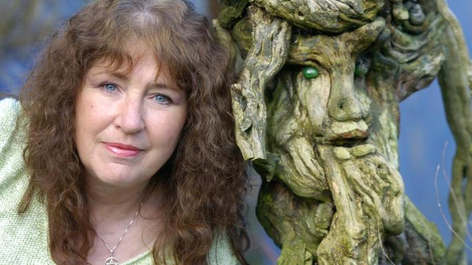 An image of Janet Paisley with a carved image of the Green Man