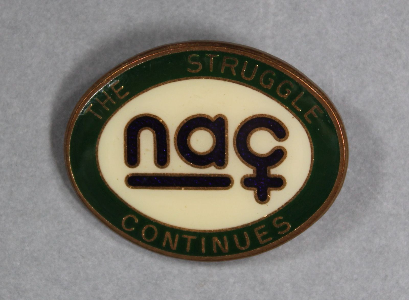 """An oval shaped badge with 'NAC' in the centre. The C is made to look like the 'woman' symbol. Around the outside of the badge it reads, """"The Struggle Continues"""""""
