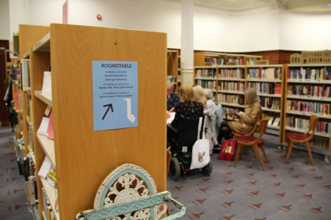 The Library space with a poster stuck to the end of one of the bookshelves. It indicates the workshops taking place in the space. In the background you can make out some women gathered around a table.