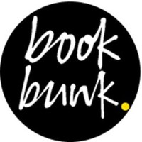 "The Book Bunk logo. A black circle with white text that reads, ""book bunk""."