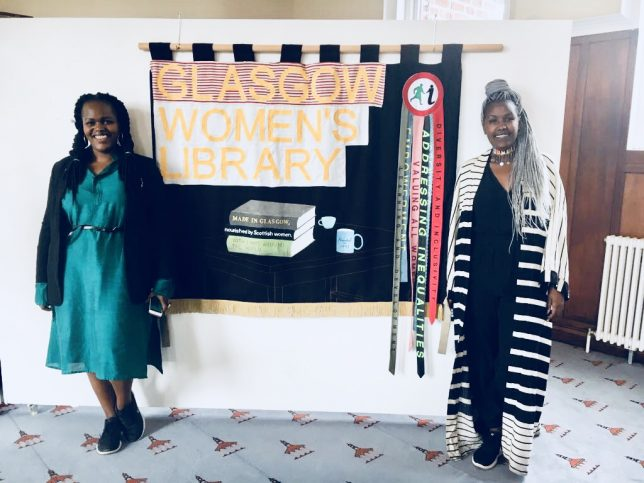 Two women standing in front of a banner that says 'Glasgow Women's Library'