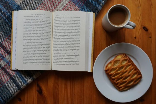 Flatlay of an open book partly lying on a tartan blanket and on a wooden table. On the right-hand side of the book are a cup of coffee and a piece of apple lattice pie on a plate.