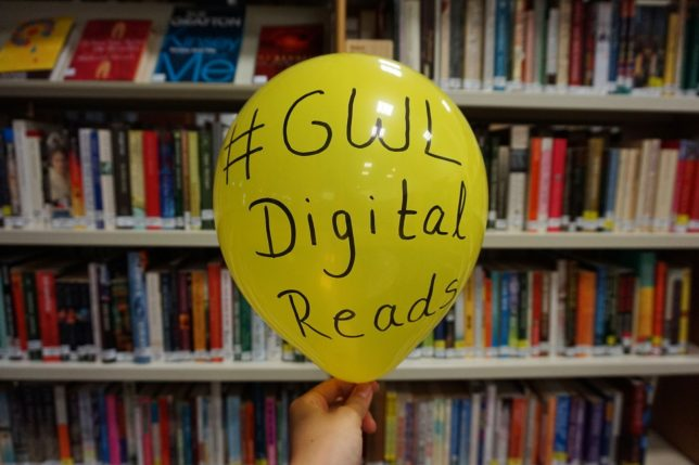 Image of a hand holding a yellow balloon in front of the library shelves. The hashtag GWL Digital Reads for the Digital Book Group is written with permanent marker on the balloon.