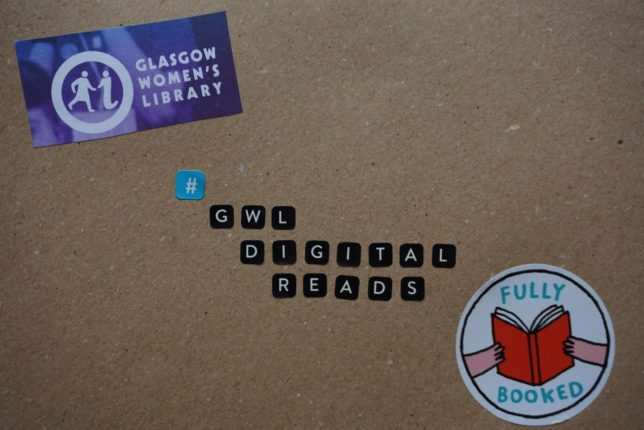 Image of a decorated piece of recycled cardboard. Stickers in the centre of the cardboard spell out the hashtag GWL Digital Reads. In the top left-hand cornern is a cut out logo of the Glasgow Women's Library. In the bottom right corner is a round sticker with an illustration of two hands holding an open book with a red cover. The sticker reads fully booked in turquoise.