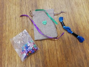 Handmade drawstring pouch with packet of beads and thread