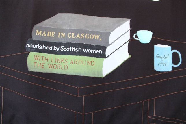 Close up section of Fiona Jack's Banner for GWL that features three books on a table. On the spines of the books is written 'Made in Glasgow, Nourished by Scottish women, With links around the world'. On a mug next to the books is written 'Founded in 1991'.