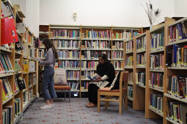 Two women in our Library space. One is sitting reading a book and another is standing and browsing the bookshelves.