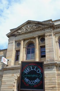 A photo of the front of GWL, with a blackboard sign saying 'Hello, Everyone Welcome' in front.