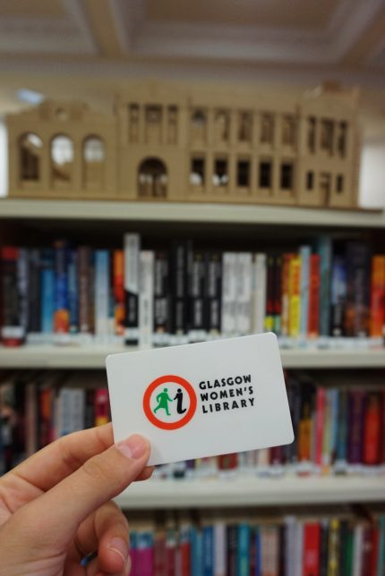 A hand holds up a GWL Borrower Card bearing the GWL logo, a red circle with a green figure of a woman and an 'i' for information. There are bookshelves and an architect's model of the building behind.