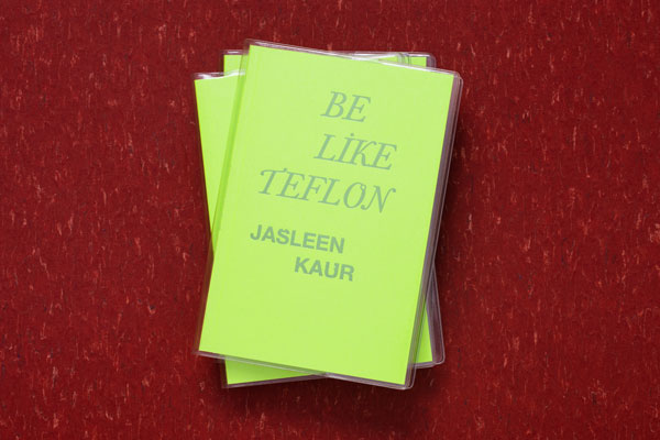 A stack of Jasleen Kau's book Be Like Teflon on a red surface. The book has a bright green cover with the text in capital letters in a silver font.