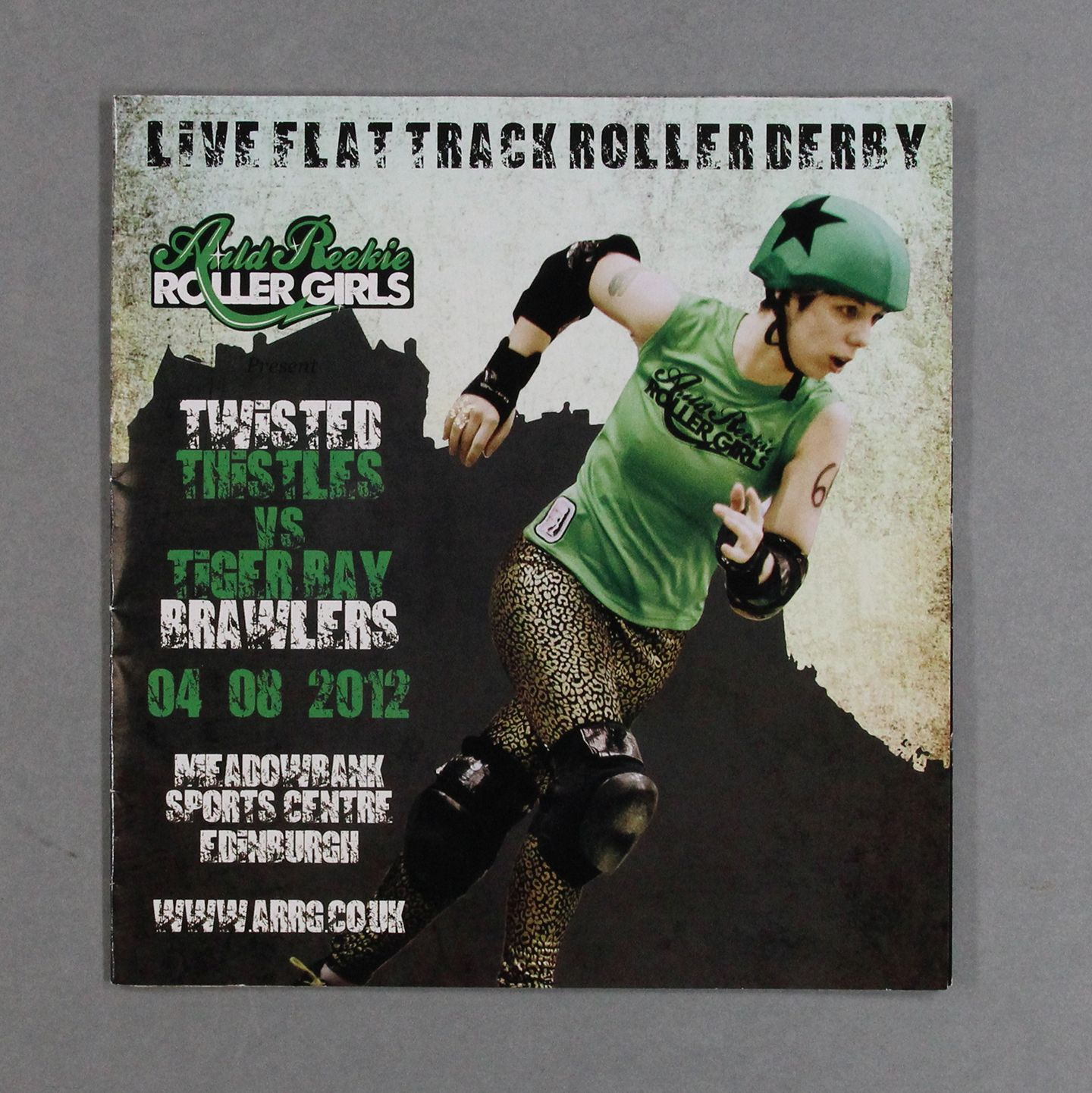 Roller Derby Bout programme cover, featuring a roller derby player in protective gear including a green helmet with a black star, wearing a sleeveless t-shirt that says 'Auld Reekie Roller Girls', and animal print leggings.