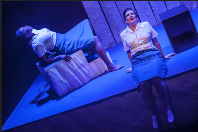 A shot from a performance. Two women sit on the stage and are lit with a blue tint.
