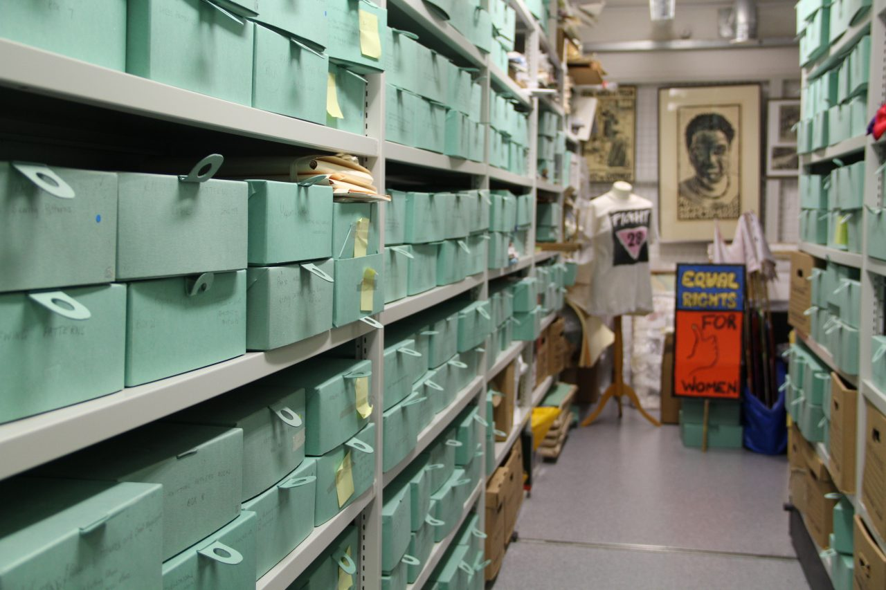 Inside one of the archive stores at GWL, with shelves full of pale green archive boxes. A t-shirt with the slogan 'Fight 28', and a placard reading 'Equal Rights for Women' are visible in the background.