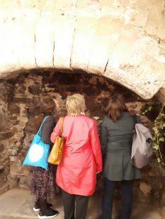 Three women look at a brick wall. We just see their backs.