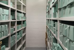 Photograph of the inside of one of GWL's archive stores showing pale green archive boxes stacked on long shelves.