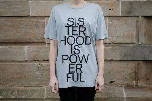 Photo of a grey t-shirt with the words Sisterhood is Powerful' on the front.