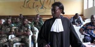 A black woman in a lawyers robe stands in front of a group of seated men in soldiers uniform.