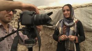 A woman with a headscarf watches as a cameraman films a sight off screen.