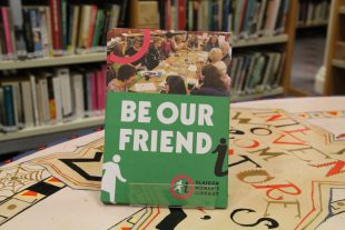 A display of GWL Friends leaflets with the title 'Be Our Friend' stands on a colourful table with bookshelves behind.