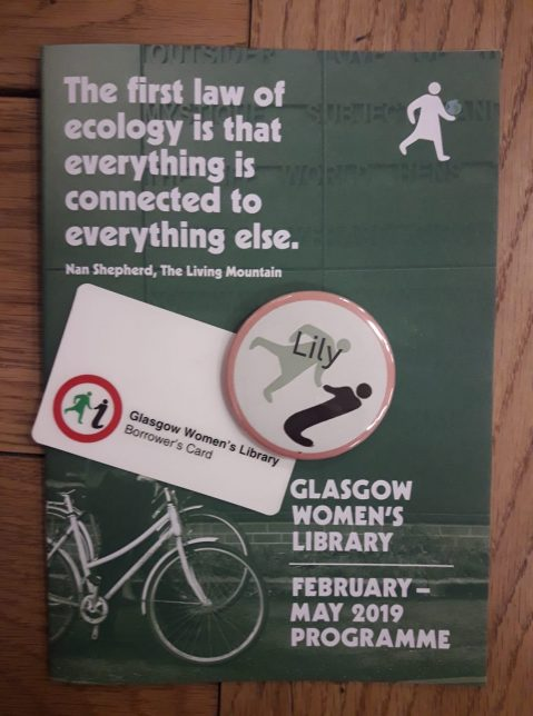 "A badge with the name ""Lily"" on it, sitting next to a GWL library card on the GWL programme of events from February to May 2019. There is a quote from Nan Shepherd on the programme: ""The first law of ecology is that everything is connected to everything else""."