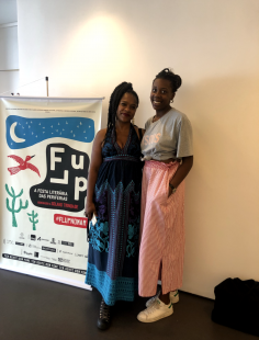 Two women standing side by side in front of a FLUP banner.