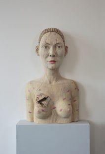 Wood carving of a woman's face and torso.
