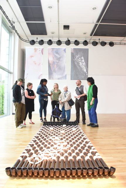 A group of adults stand together in a gallery, there is an artwork on the floor similar to a raft made from black rain pipes tied together with pink fabric.