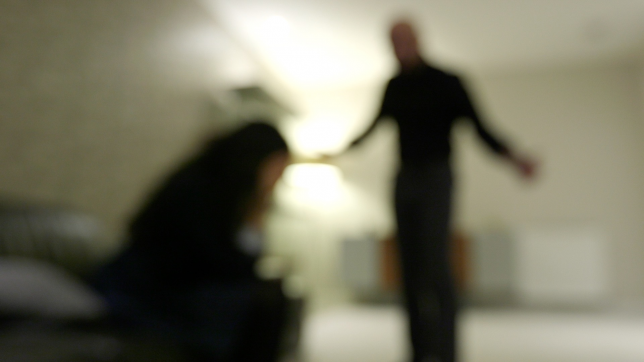 Still from the film Shifting Sands - the image is blurry, but you can make out the figure of a man standing over a woman who is hunched in on herself.